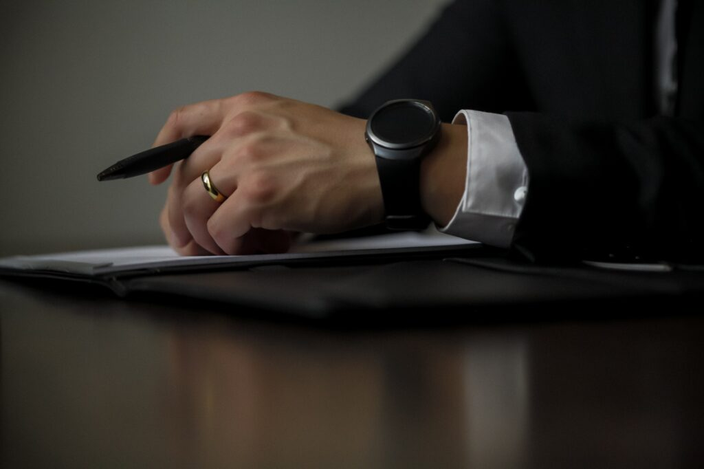 photo of a person wearing a suit and black watch with documents