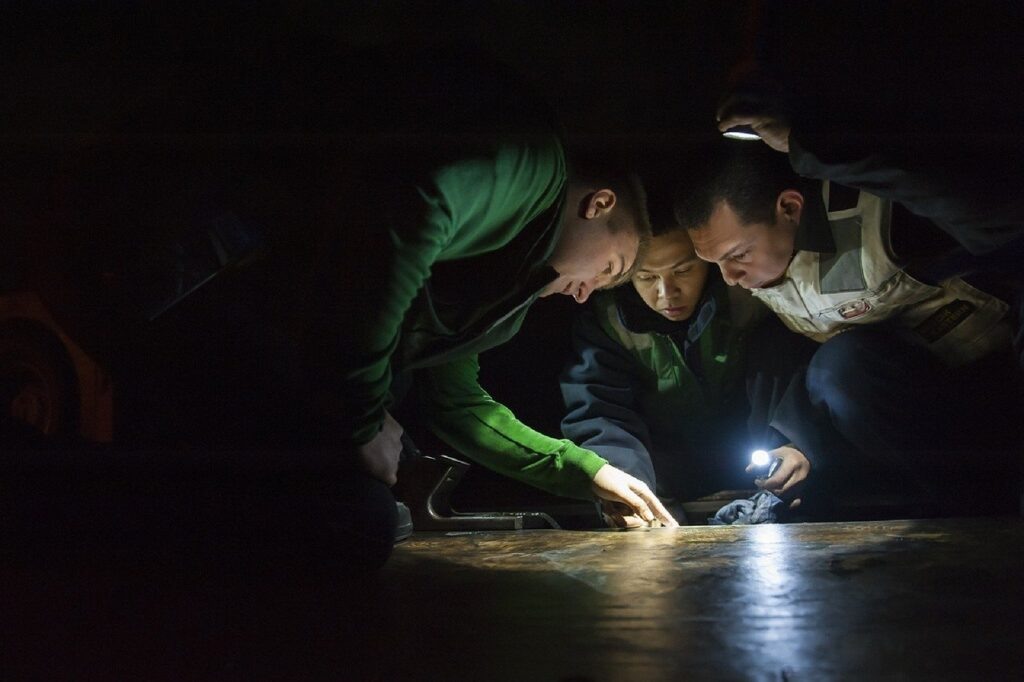 maintenance workers inspecting floor flashlights
