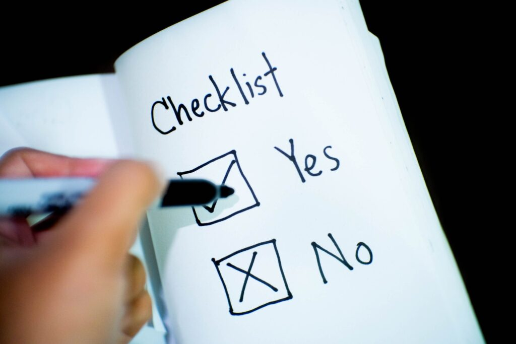 checklist on notebook person holding black pen