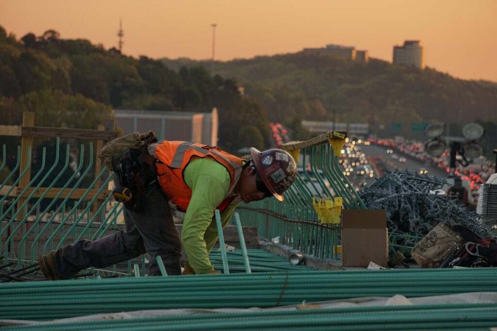 construction worker on top of a building during sunset