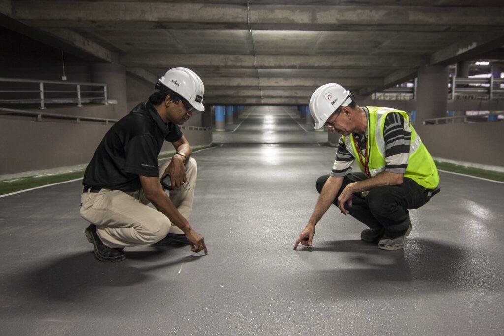 men looking at floor construction worker inspection