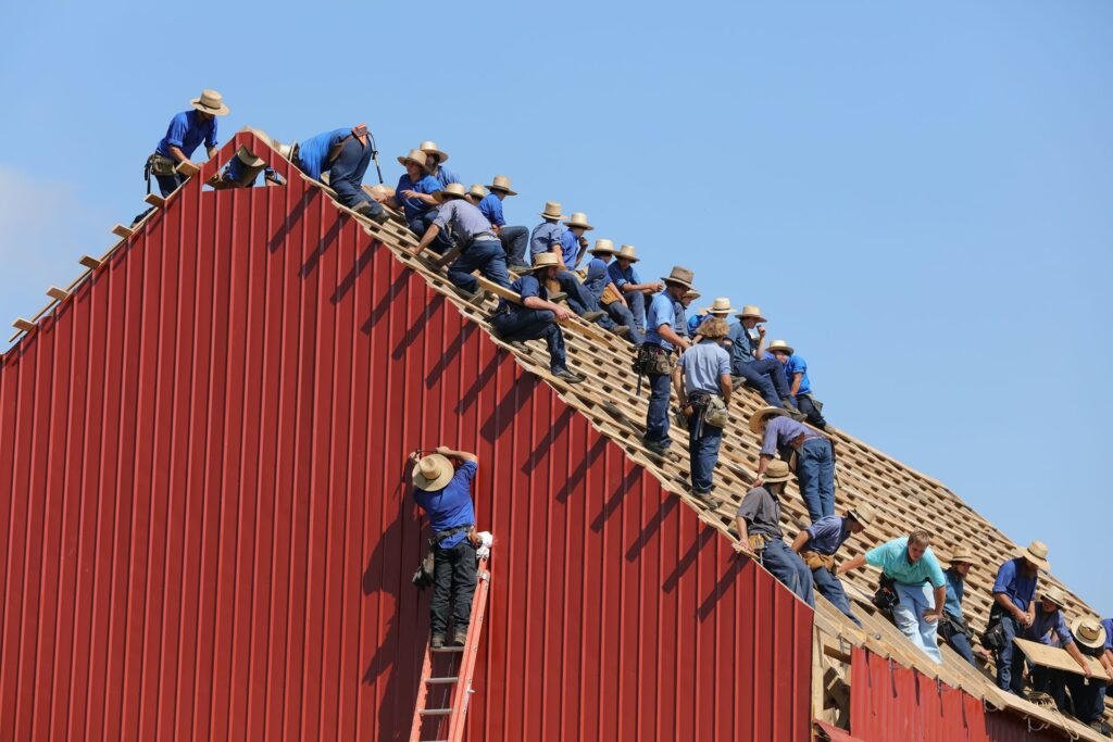 people on top of a roof building construction