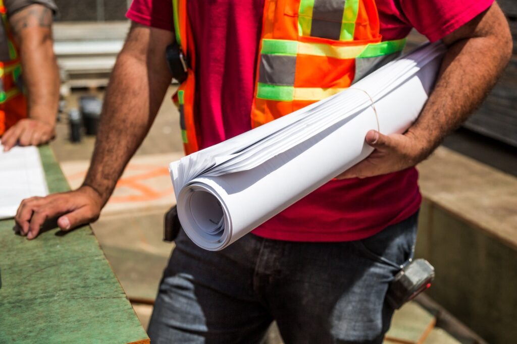 person holding drafting paper construction worker