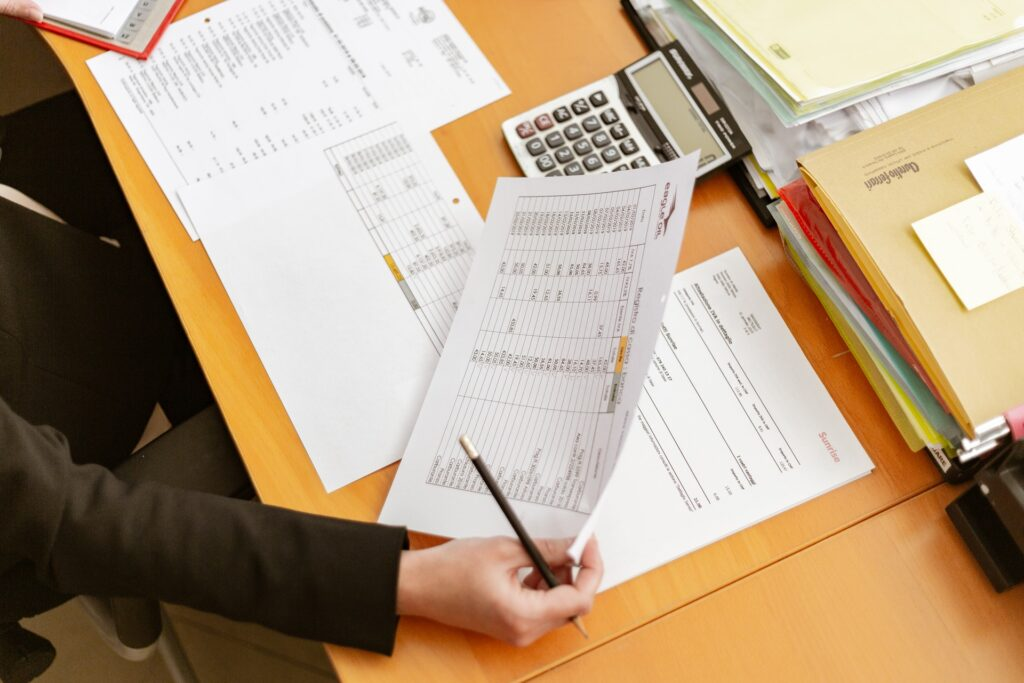 person holding pen and paper on desk