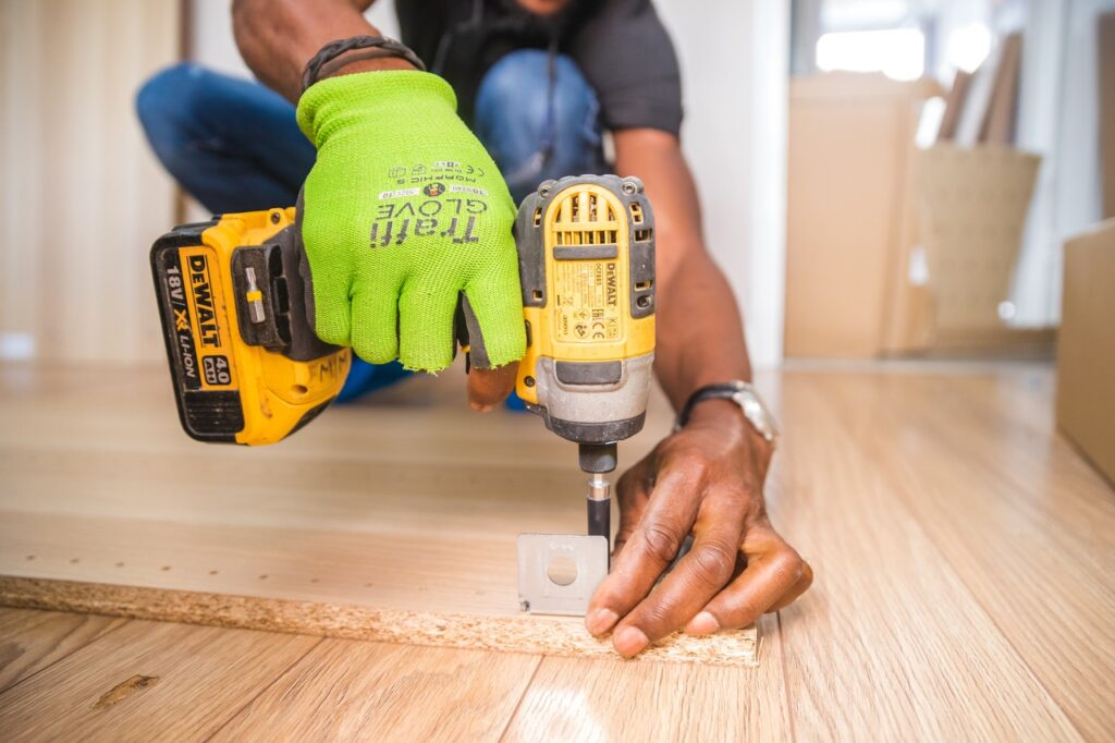 person using dewalt cordless impact-driver on brown board