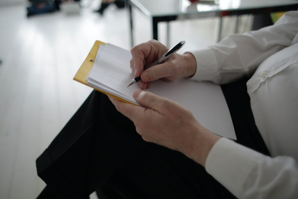 person writing on checkboard checklist blank paper