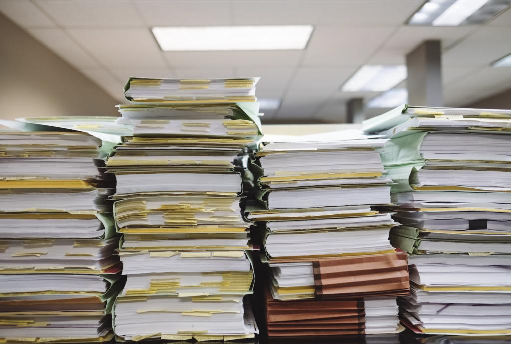 stacks of paper piled up on desk