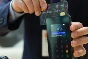 credit card in hand being swiped penalty payment