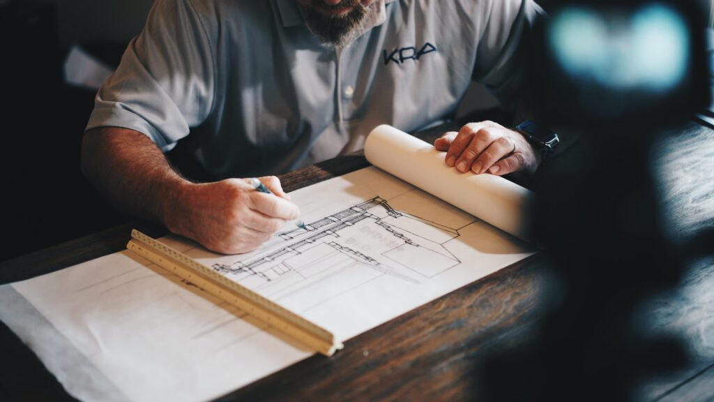 man looking at construction papers holding a pencil